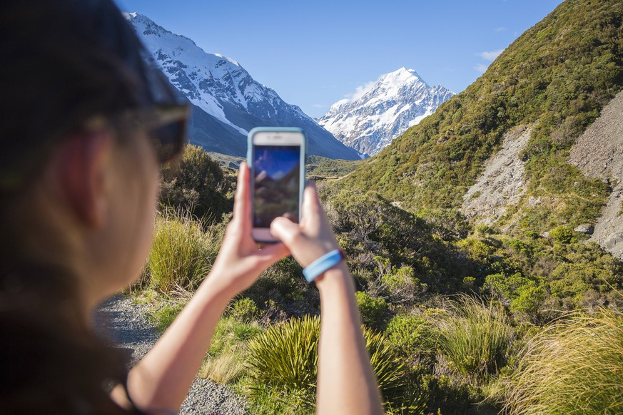 Over the shoulder view of young woman taking picture of Mount Cook with smartphone, Hooker Valley Track, Canterbury, New Zealand, Mt. Cook Village Canterbury New Zealand model released Symbolfoto PUBLICATIONxINxGERxSUIxAUTxONLY Copyright: GrantxOrdelheide ORGR000222