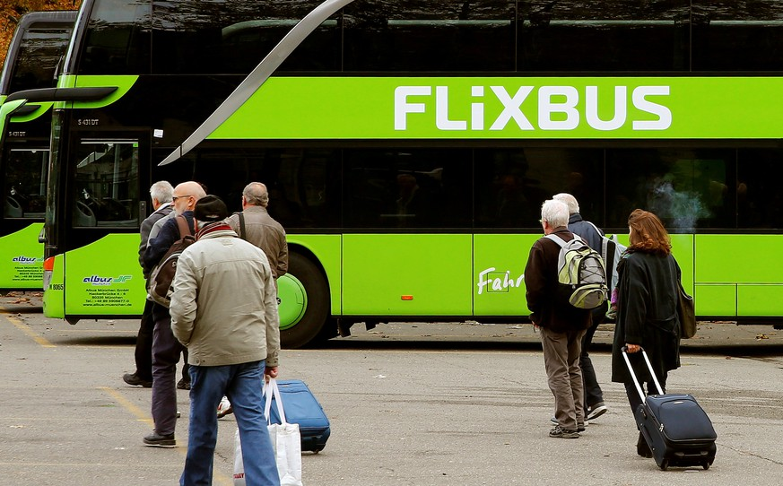 FILE PHOTO: Passengers walk in front of a FlixBus intercity bus at the Carparkplatz Sihlquai bus station in Zurich, Switzerland October 27, 2016.  REUTERS/Arnd Wiegmann/File Photo