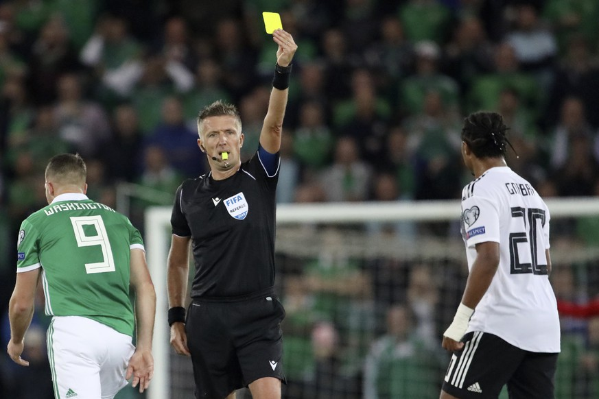Referee Daniele Orsato shows a yellow card to Germany's Serge Gnabry, right, during the Euro 2020 group C qualifying soccer match between Northern Ireland and Germany at Windsor Park, Belfast, Northern Ireland, Monday, Sept. 9, 2019. (AP Photo/Peter Morrison)
