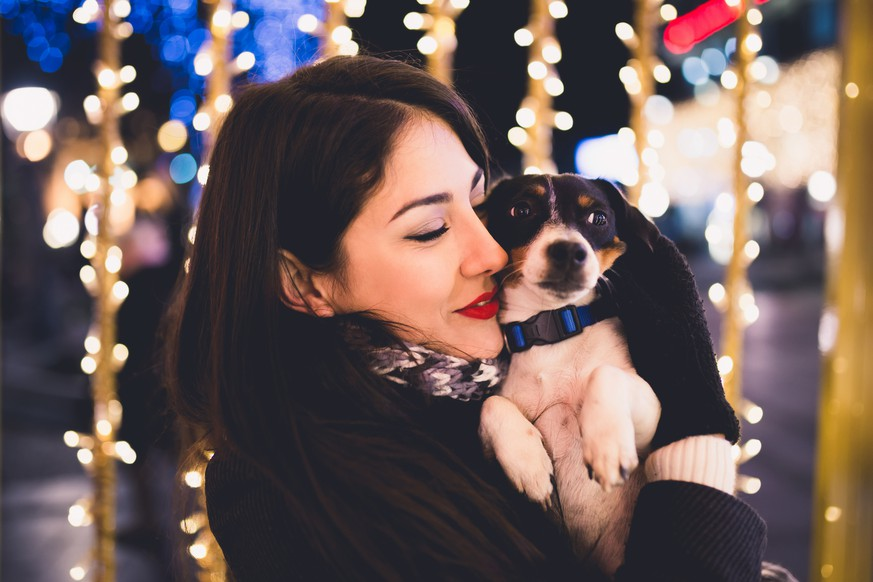 Beautiful young brunette woman with Jack Russell terrier enjoying Christmas or New Year night ona a city street.