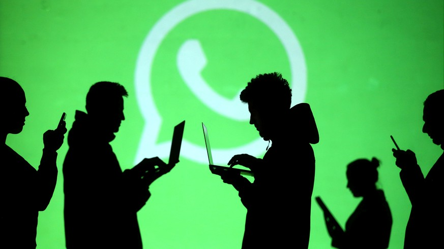 FILE PHOTO: Silhouettes of laptop and mobile device users are seen next to a screen projection of Whatsapp logo in this picture illustration taken March 28, 2018.  REUTERS/Dado Ruvic/File Photo