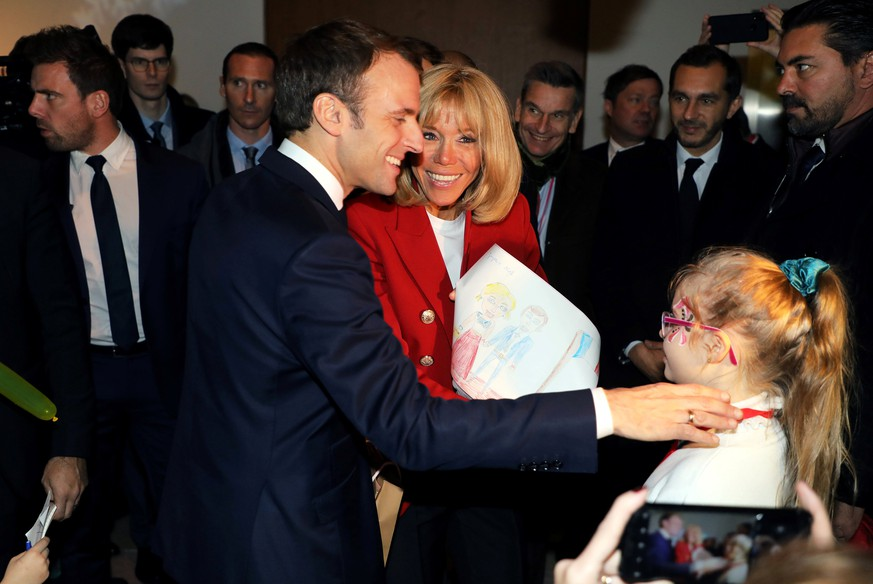 French President Emmanuel Macron and his wife Brigitte Macron receive a drawing as a present from a girl during the Christmas Party for the children of Elysee Palace's employees at the Gobelins Manufactory, in Paris, France, December 19, 2018. Ludovic Marin/Pool via REUTERS