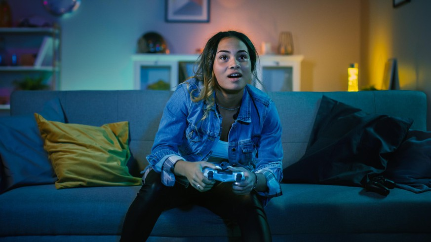 Beautiful Excited Young Black Gamer Girl Sitting on a Couch and Playing Video Games on a Console. She Plays with a Wireless Controller. Cozy Room is Lit with Warm and Neon Light.