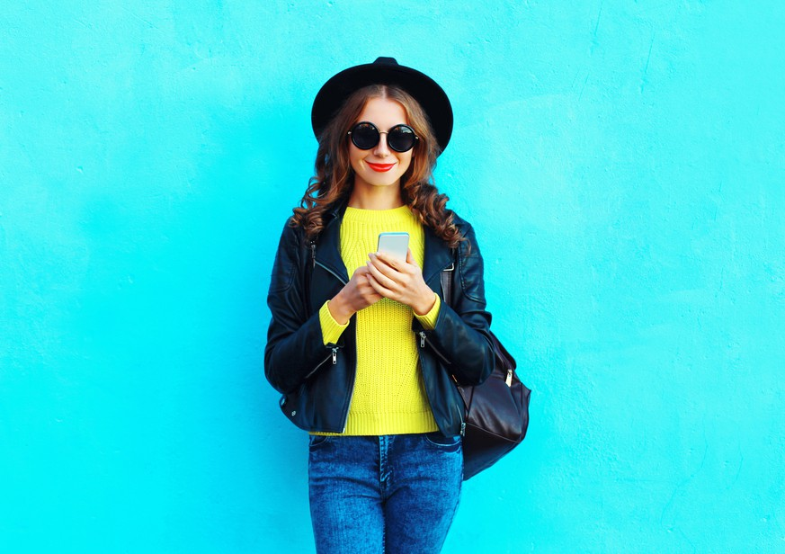 Fashion pretty woman using smartphone wearing a black rock style clothes over colorful blue background