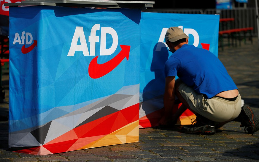 A man helps to set up banners at an election campaign of Germany's far-right Alternative For Germany (AFD) party ahead the upcoming Saxony state elections in Dresden, Germany, August 25, 2019. REUTERS/Hannibal Hanschke