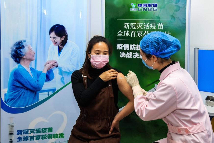 201231 -- BEIJING, Dec. 31, 2020  -- A volunteer receives the COVID-19 vaccine developed by Wuhan Biological Products Institute Co., Ltd. in Wuzhi County, central China s Henan Province, April 12, 2020. China announced on Thursday that it had granted conditional marketing authorization for its first self-developed COVID-19 vaccine. The inactivated vaccine, which got the approval from the National Medical Products Administration NMPA, is developed by the Beijing Biological Products Institute Co., Ltd. under the China National Biotec Group CNBG, which is affiliated with Sinopharm. The COVID-19 vaccines will be provided free of charge to all Chinese people, said Zeng Yixin, deputy head of the National Health Commission.  CHIN PUBLICATIONxNOTxINxCHN