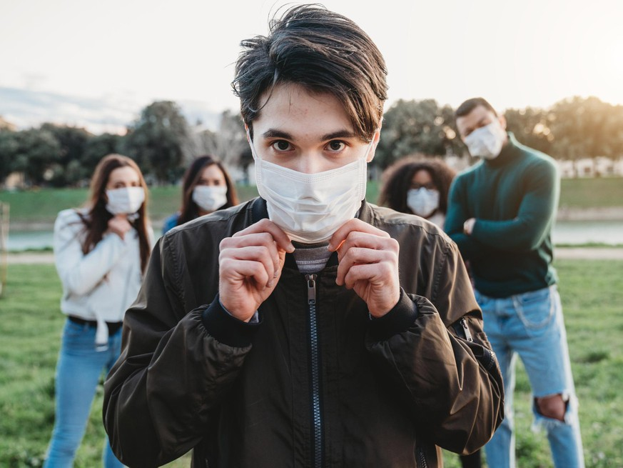 Young adult man wearing a pollution mask to protect himself from viruses. His friends are in the background. They all are wearing masks. Conceptual image of protection against pandemic virus.