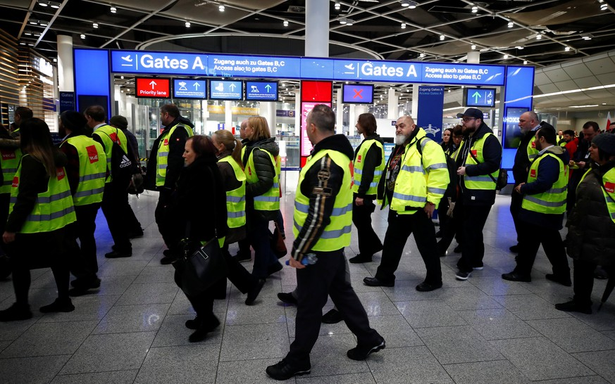Members of Germany's union Verdi wear yellow vests as they march in front of Gate A of Duesseldorf Airport during a strike by Verdi, which called on security staff at Duesseldorf, Cologne and Stuttgart airports to put pressure on management in wage talks, in Duesseldorf, Germany January 10, 2019. REUTERS/Wolfgang Rattay