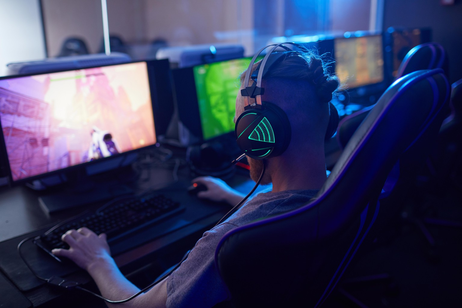 Rear view of young gamer wearing gaming headphones with backlight and playing in computer video game on computer in dark computer class