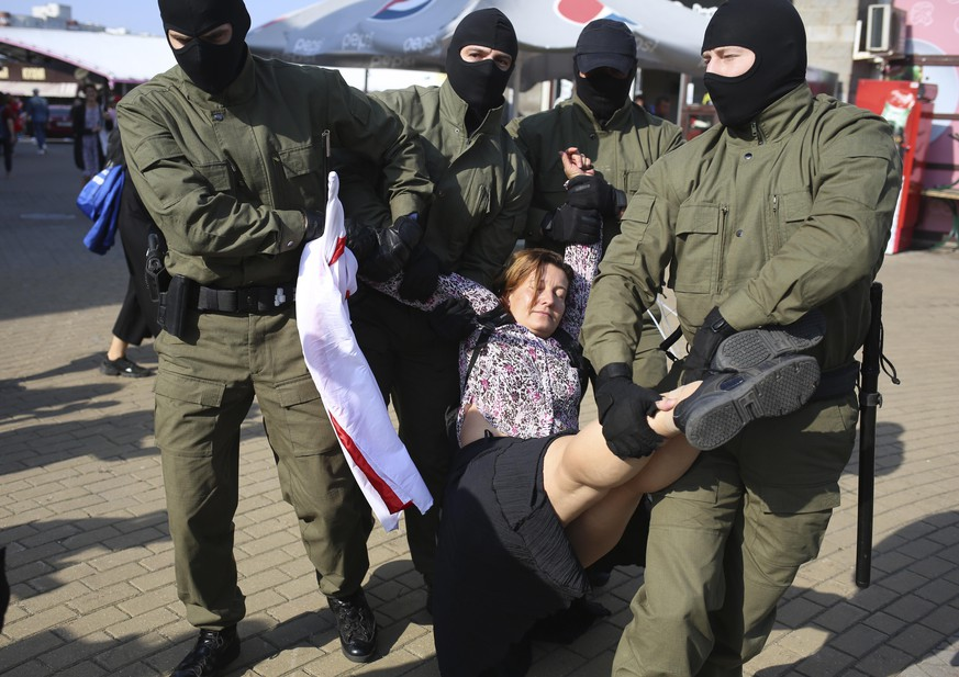 Police officer detain a woman with an old Belarusian national flag during an opposition rally to protest the official presidential election results in Minsk, Belarus, Saturday, Sept. 26, 2020. Hundreds of thousands of Belarusians have been protesting daily since the Aug. 9 presidential election. (AP Photo/TUT.by)