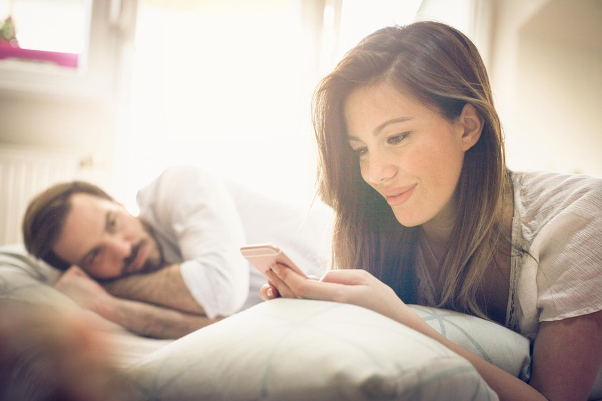 Young couple in bed. Focus on woman. Space for copy.
