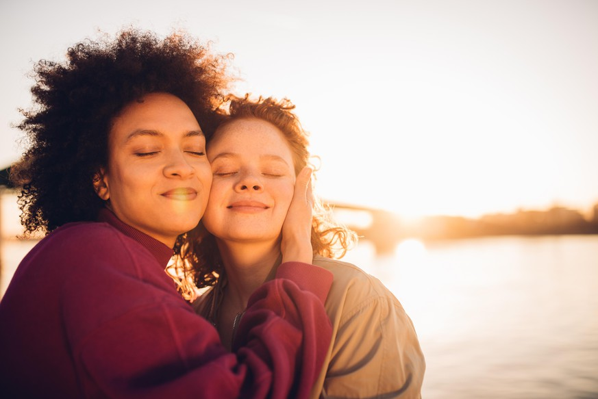 Portrait of two girls hugging and enjoying the sunset together.