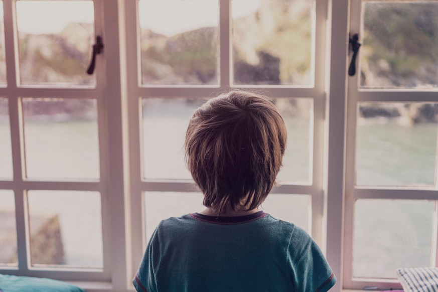 A young boy looking out of the window of a cottage by the coast.