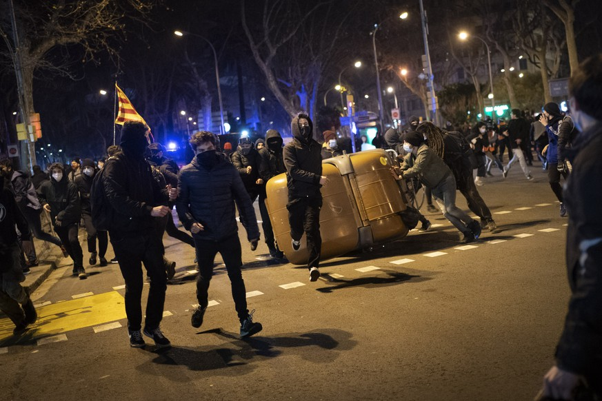 Demonstrators made barricades during clashes with police following a protest condemning the arrest of rap singer Pablo Hasél in Barcelona, Spain, Wednesday, Feb. 17, 2021. Police fired rubber bullets and baton-charged protesters as clashes erupted for a second night in a row Wednesday at demonstrations over the arrest of Spanish rap artist Pablo Hasél. Many protesters threw objects at police and used rubbish containers and overturned motorbikes to block streets in both Madrid and Barcelona. (AP Photo/Emilio Morenatti)