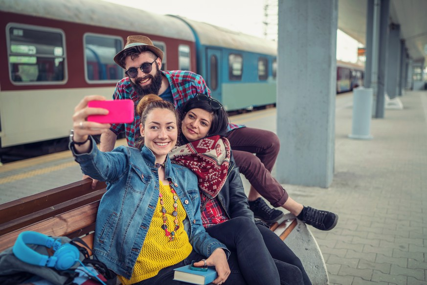 Cheerful young travelers waiting at the railway platform and making selfies