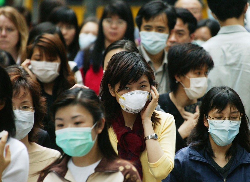 HONG KONG - APRIL 1:  People wear surgical masks to try to reduce the chance of infection from SARS (Severe Acute Respiratory Syndrome)whilst walking through the business district April 1, 2003 in Hong Kong. People have been warned of the importance of personal hygiene and have been told to limit the time they spend in crowded public areas, or avoid them completely if possible. (Photo by Christian Keenan/Getty Images)