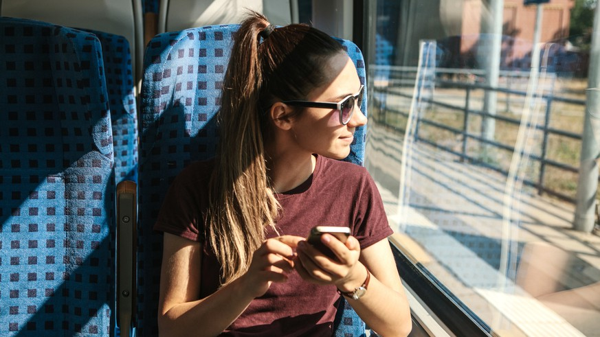 A young girl rides a train and uses a mobile phone. Train ride.