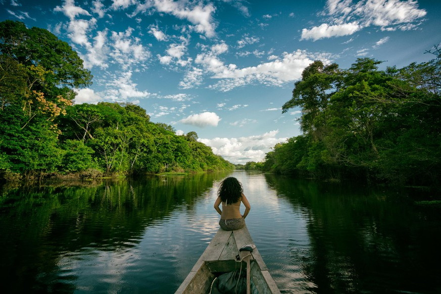 Sailing in a wooden boat on the Amazon river in Peru. An indigenous girl sitting on the front of the boat whilst sailing down the river.